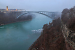 The bridge to Canada over the Niagara River on a rainy, foggy winter day at Niagara Falls, New York State, USA