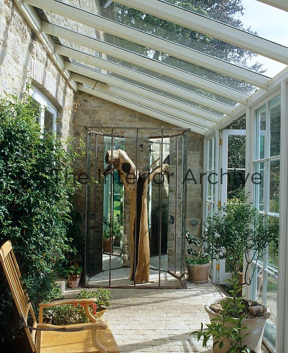 A wooden sculpture made from a tree trunk in a metal and mirror cage has been placed in the conservatory