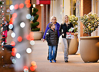 STAFF PHOTO BEN GOFF  @NWABenGoff -- 12/03/14 Natalie Greene, son Luke Greene, 9, and mother Jimmie Huber of Rogers shop after visiting Santa Claus with Luke's sister Norah Greene, 6, who ran ahead, at Pinnacle Hills Promenade in Rogers on Wednesday Dec. 3, 2014.
