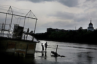 Two boys fishing from a wrecked houseboat on the Dnister  (Nistru) River.