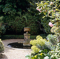 A sculpture of a heron is concealed in the shrubs behind the small garden pond