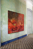 An unframed painting hangs on the distressed plaster wall of the entrance hall