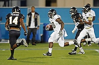30 March 2012:  FIU's Shane Coleman (20) attempts to evade Demarkus Perkins (14) on a long touchdown run at the FIU Football Spring Game at University Park Stadium in Miami, Florida.