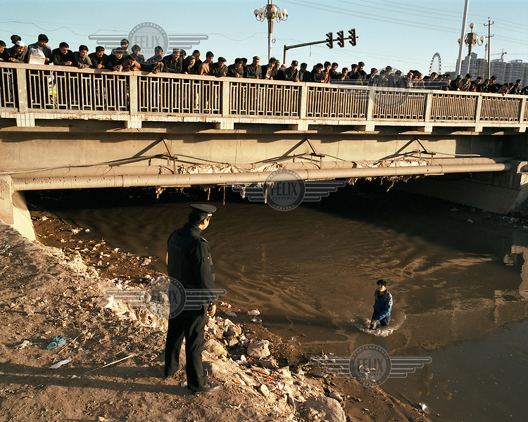 A crowd gathers at one of the main bridges in Kashgar. A Uighur (Uyghur) boy has ended up in the river, claiming that a Chinese policeman threw him in.