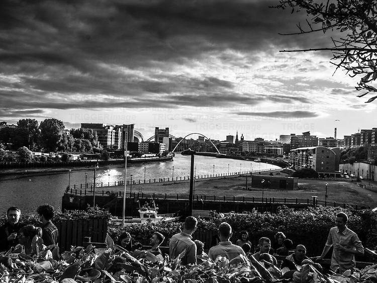 People relaxing with a view over the river Tyne in Newcastle England