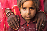 Rajasthani woman holding hands on her son's shoulders, Rajasthan, India --- Model Released