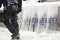 A policeman in anti-riot gear walks by police shield during a protest in Quebec City Monday December 6, 2010.
