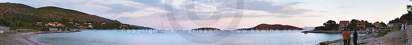 Wide panorama of the bay and the beach with people standing on the beach, a sailing boat moored in the bay islands in the background, off the Korcula island at sunset. Prizba village. Korcula Island. Prizba, Riva Apartments, Danny Franulovic. Korcula Island. Dalmatian Coast, Croatia, Europe.