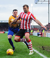 Lincoln City's Matt Rhead shields the ball from Mansfield Town's Matt Preston<br /> <br /> Photographer Chris Vaughan/CameraSport<br /> <br /> The EFL Sky Bet League Two - Lincoln City v Mansfield Town - Saturday 24th November 2018 - Sincil Bank - Lincoln<br /> <br /> World Copyright &copy; 2018 CameraSport. All rights reserved. 43 Linden Ave. Countesthorpe. Leicester. England. LE8 5PG - Tel: +44 (0) 116 277 4147 - admin@camerasport.com - www.camerasport.com