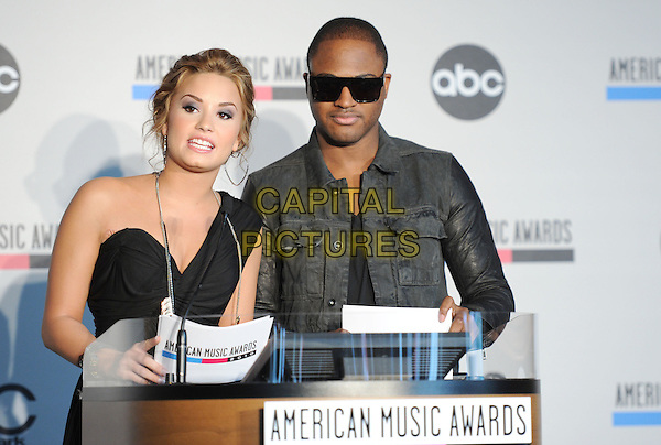 DEMI LOVATO & TAIO CRUZ .at The 2010 American Music Award Nomination Announcements held at The JW Marriott Los Angeles at L.A. Live in Los Angeles, California, USA, .October 12th 2010..half length dress black one shoulder sunglasses jacket denim leather sleeves  microphone podium  .CAP/RKE/DVS.©DVS/RockinExposures/Capital Pictures.