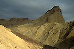 Sunlight and storm clouds on eroded hills below Zabriskie Point, Golden Canyon, Death Valley, California