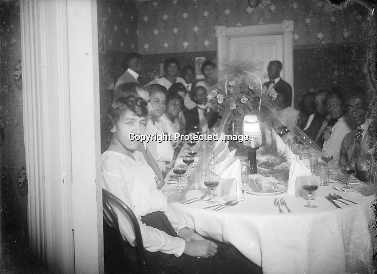 DINNER PARTY. This image records a very elaborately set table, as well as the numerous guests. The lady in the foreground is probably Eva O'Donnell, whose parents James and Susan O'Donnell resided at 623 C Street, in the South Bottoms neighborhood. The house still stands. Mr. O'Donnell was the proprietor of a &quot;lunch stand&quot; in downtown Lincoln.<br /> <br /> Photographs taken on black and white glass negatives by African American photographer John Johnson from 1910 to 1925 in Lincoln, Nebraska. Douglas Keister has 280 5x7 glass negatives taken by these photographers. Larger scans available on request.