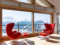 A pair of Arne Jacobsen Egg chairs with matching footstools has been placed beside the plate glass window with a spectacular view of the Alps