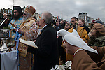 Greek community Uk. Margate Kent. Greek Orthodox Church of the Archangel Michael  A white dove a symbol of peace is released at the The Blessing of the Sea ceremony to celebrate Epiphany (6th January) L - R  The Very Revd. Archimandrite Vissarion Kokliotis, ( in blue robes) The Greek Archbishop Gregorios of Thyateira and Great Britain,  Mr Michael Papadopoullos, president of Margate's Greek Community with bible open.