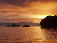 Sunrise over Maxwell Bay off King George Island, Antarctica. A ship is anchored in the bay. DCF