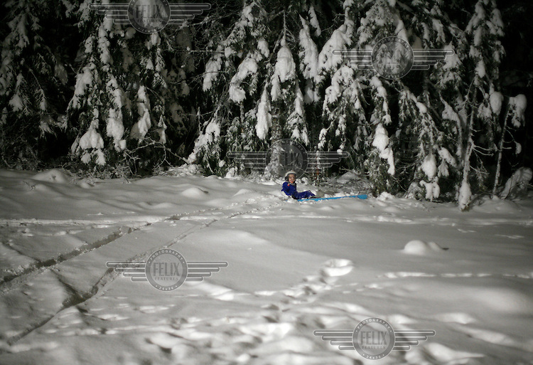 Oscar  Mortensen (10)  ski jumping in Schroderbakken, nearly ends up in the forest after landing.  Near the center of Oslo, Norway.
