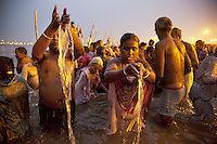 "India. Uttar Pradesh state. Allahabad. Maha Kumbh Mela. Royal bath on Basant Panchami Snan (fifth day of the new moon). The ritual ""Royal Bath"" is timed to match an auspicious planetary alignment, when believers say spiritual energy flows to earth. An Indian Hindu devotee couple takes a holy dip in Sangam at sunrise. The woman wearing a saree and her husband offer water to Mother Ganges, because the river is considered as a deity. The Kumbh Mela, believed to be the largest religious gathering is held every 12 years on the banks of the 'Sangam'- the confluence of the holy rivers Ganga, Yamuna and the mythical Saraswati. In 2013, it is estimated that nearly 80 million devotees took a bath in the water of the holy river Ganges. The belief is that bathing and taking a holy dip will wash and free one from all the past sins, get salvation and paves the way for Moksha (meaning liberation from the cycle of Life, Death and Rebirth). Bathing in the holy waters of Ganga is believed to be most auspicious at the time of Kumbh Mela, because the water is charged with positive healing effects and enhanced with electromagnetic radiations of the Sun, Moon and Jupiter. The Maha (great) Kumbh Mela, which comes after 12 Purna Kumbh Mela, or 144 years, is always held at Allahabad. Uttar Pradesh (abbreviated U.P.) is a state located in northern India. 15.02.13 © 2013 Didier Ruef"
