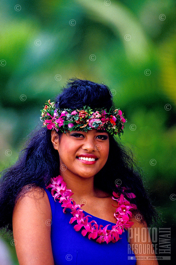 A beautiful young Samoan woman wearing a pink lei and haku lei smiles against a background of muted green foliage.