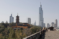 Visitors walk on the massive city wall against a backdrop of Jiming Temple (L) and the new business district in Nanjing, Jiangsu province, China, November 2012.