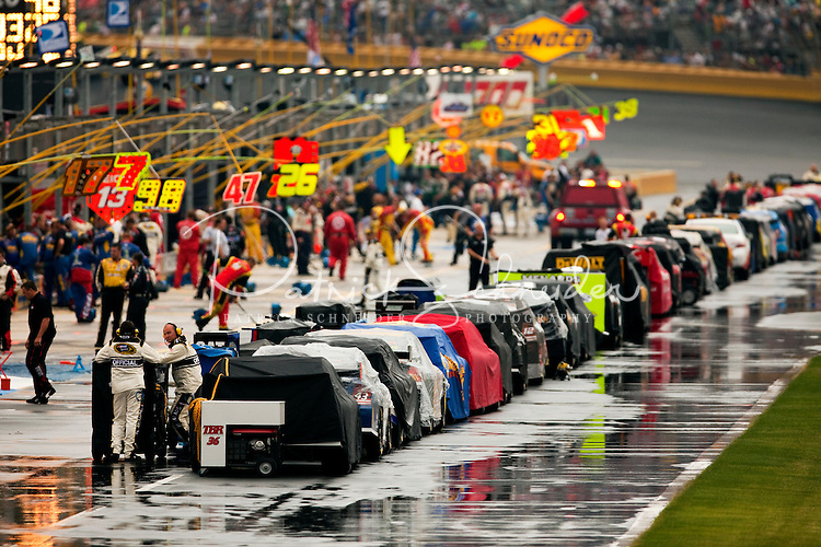 NASCAR race teams wait out a rain shower in pit row at the Lowe's Motor Speedway, in Concord, NC, during the 2009 Coca-Cola Classic 600 NASCAR race. Driver David Reutimann won his first Cup race during the rain-shortened event, held May 25, 2009. NASCAR's longest scheduled race went only 227 laps, or 340.5 miles, before officials ended it because of rain. The 2009 race was the 50th running of the Coca-Cola 600. Ryan Newman and Robby Gordon finished second and third respectively.
