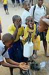 Tansania, Kinder spielen mit Wasser auf Schulhof in Schule in Dar es Salam / Tanzania, kids play with water at school in Dar es salam