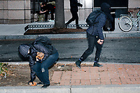 Antifa activists pry up bricks from a sidewalk to throw at police during protests after in the inauguration of President Donald Trump on Jan. 20, 2017, in Washington, D.C.