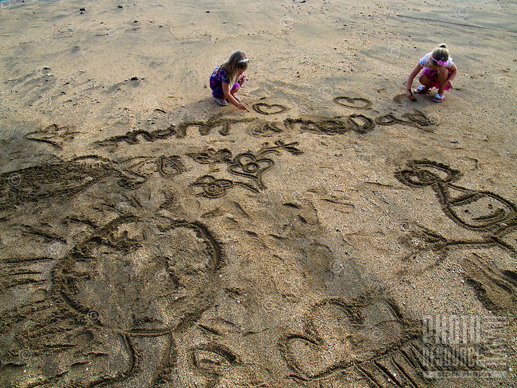 Two young girls draw in the sand at Old Airport beach, Big Island.