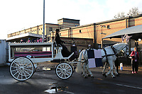 The horse and carriage carrying the pink and blue coffin stops in the car park alongside the entrance to the ground during the funeral of Dulwich Hamlet FC supporter Mishi Morath at Champion Hill Stadium on 15th January 2020