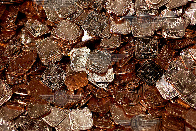 A mound of newly made Five Cent coins, made for the government of Suriname, in a container at the Royal Mint, near Llantrisant in Mid Glamorgan. As well as producing coinage for domestic use the mint also manufactures coins for around 60 countries worldwide.