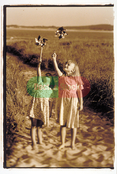 young girls playing with pinwheels at beach