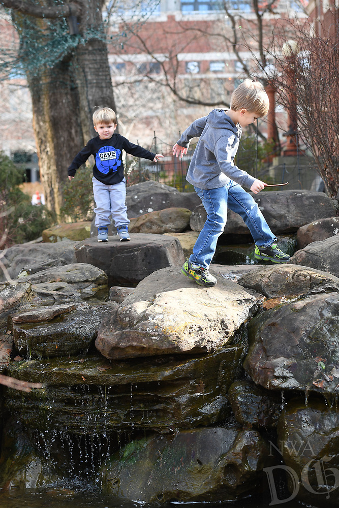 NWA Democrat-Gazette/J.T. WAMPLER A.J. O'Bryan, 5, (RIGHT) plays with his brother Sinclair O'Bryan, 3, Sunday Jan 6, 2019 on the water feature on the Fayetteville Square. The brothers were there with their dad, Will O'Bryan of Fayetteville. According to the National Weather Service, warm temperatures and sunny skies will be lingering this week.