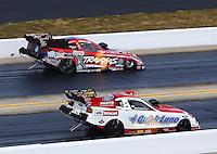 Sep 15, 2013; Charlotte, NC, USA; NHRA funny car driver Courtney Force (far lane) races alongside Bob Tasca III during the Carolina Nationals at zMax Dragway. Mandatory Credit: Mark J. Rebilas-