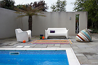 A white moulded plastic sofa and armchair are situated beside the cobalt blue waters of the geo-thermically heated pool
