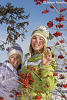 Happy young girls posing beside a mountain ash berry tree in winter