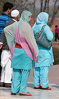Agra, India.  Taj Mahal.  Indian women wearing a shalwar kameez, loose trousers topped by a long, loose shirt.  They cover their head and shoulders with a scarf-like garment called a dupatta.