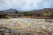 The East Branch of the Pemigewasset River in Lincoln, New Hampshire USA after hours of heavy rains and strong winds from Hurricane Sandy in 2012. Hurricane Sandy caused massive destruction along the east coast. This bridge at the entrance to Loon Mountain Ski Area was damaged during Tropical Storm Irene in 2011.