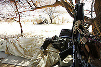 an SLA ( sudan liberation army) rebel takes a rest under a tree in a forwading base on in nirth darfur on Nov 2004