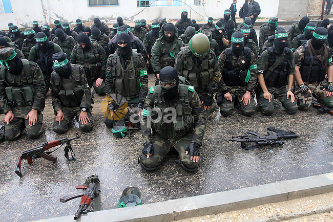 Palestinian members of al-Qassam Brigades, the armed wing of the Hamas movement, pray during a military parade marking the 27th anniversary of Hamas' founding, in Gaza City December 14, 2014. Photo by Mohammed Asad