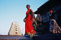 Indian women walk past a Hindu Temple in the backgroind. Belur, India.