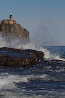 Split Rock Lighthouse with waves crashing on shore.