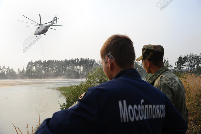 Volunteers and members of the Emergency Services fought forest fires near the village of Plotava in the east of the Moscow region as fires continued to spread as the unrelenting hot weather continued in central Russia, here a helicopter came to pick up water from a pond. 05 August 2010