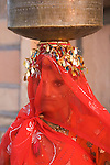 Rajasthani woman carrying water jug on head; for a married woman it is common to cover her face with a veil in front of strangers, Rajasthan, India --- Model Released