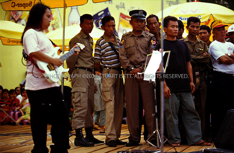 4/13/2002--Rangoon, Burma..Authorities watch fans wearily while Chit San Muang, Burma's most famous guitarist (right),belts out a tune during an Iron Cross concert...The annual outdoor free concerts are held every April duirng Burma's traditional New Year celebrations. Normally gatherings of young men woiuld be broken up by Burma's ruling junta but the concerts are the one time of year such large gatherings are allowed. Local authorities are nervous that such concerts may turn political or violent and watch the shows carefull for signs of unrest...All photographs ©2003 Stuart Isett.All rights reserved.