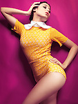 High fashion photo of a young woman wearing bright yellow vintage style clothes on pink background