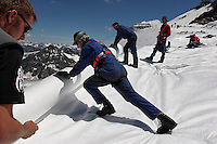Workers wrap Brunnenkogel Ferner with a fleece-like cover to keep it from melting.  Rolls of the material are attached it to the top of the part of the glacier to help save the ski industry since the glacier is retreating.  <br /> Brunnenkogel Ferner--(Austrian word for glacier )is being wrapped with a fleece-like cover to keep it from melting.  Workers unwrapped rolls of the material and attached it to the top of the part of the glacier.  The parts covered melt slower than if not covered. The ski area at 3,400 meters is covered by the thirteen workers to help save the ski industry since the glacier is retreating.  The cost of materials is one Euro per square meter...The Alpine glaciers -- in Austria, Switzerland, France and Italy -- are losing one percent of their mass every year and, even supposing no acceleration in that rate, will have all but disappeared by the end of the century...More hot, dry summers like that of 2003 in Europe, when the loss speeded to five percent, could cut the life expectancy to no more than 50 years, according to Wilfried Haeberli of the University of Zurich...&quot;We estimate that by the end of the 21st century, with a medium-type climate scenario, about five percent of what existed in the 1970s will have survived, he added.