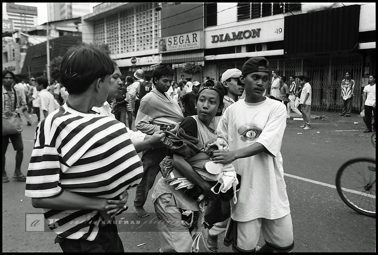 Summer '98-- Jakarta, Indonesia -- Looters steal goods from Jakarta shops and then fight over the goods in the street.
