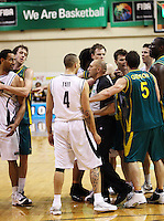 Tall Blacks forward Mika Vukona (far left) and Boomers forward Nathan Jawai (far right) are separated after a disagreement as referee Gavin Whiu (centre) steps in during the International basketball match between the NZ Tall Blacks and Australian Boomers at TSB Bank Arena, Wellington, New Zealand on 25 August 2009. Photo: Dave Lintott / lintottphoto.co.nz