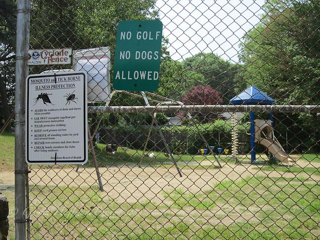 Mosquito & tick warning sign at playground.