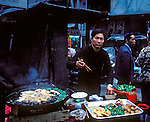 Chinese food vendor in Hong Kong cooks using a large wok over an open flame.
