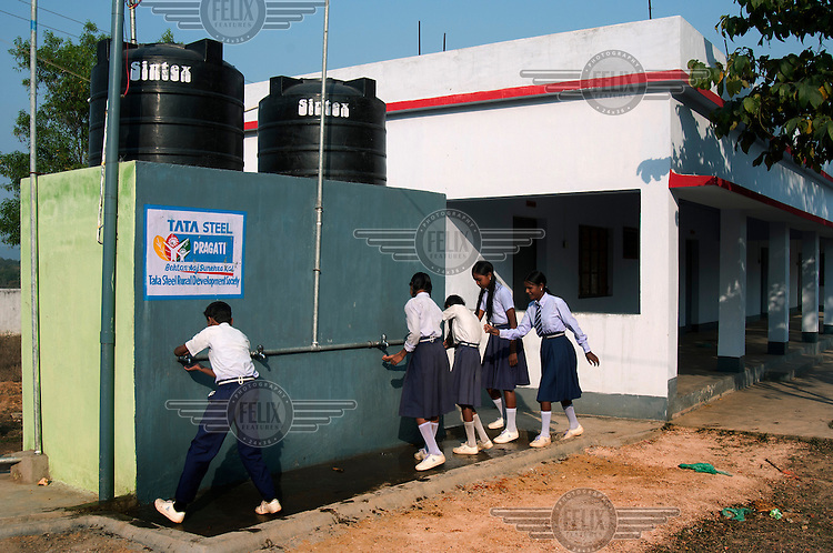 School children, at Binapani School, using water from storage tanks supplied and constructed by TSRDS (Tata Steel Rural Development Society). TSRDS is involved in various social development programmes aimed at helping the rural communities living around Tata Steel's operational units.